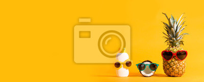 Fototapeta Pineapple and coconut wearing sunglasses with sunblock on a solid background