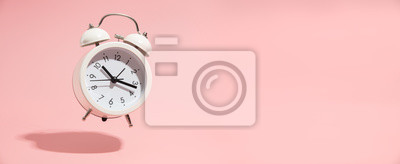 Fototapeta Pink Alarm clock on pastel pink background.