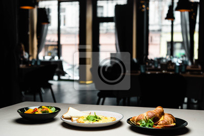 Fototapeta plates with salad, omelet and croissants for breakfast on table in restaurant