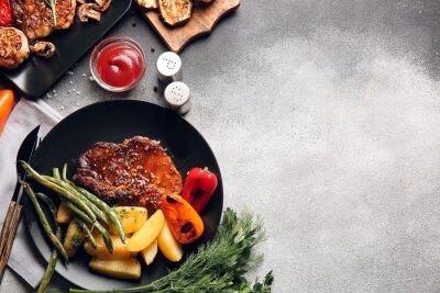 Fototapeta Plates with tasty pork steaks and grilled vegetables on grey background