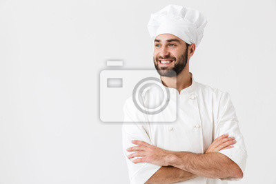 Fototapeta Pleased happy young chef posing isolated over white wall background in uniform.