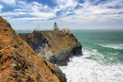 Fototapeta Point Bonita Lighthouse outside San Francisco, California stands at the end of a beautiful suspension bridge.