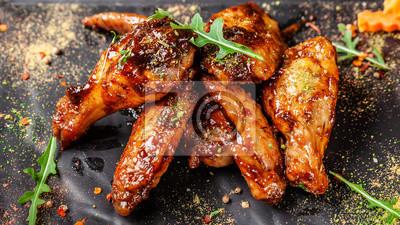 Fototapeta Pojęcie kuchni indyjskiej. Pieczone skrzydełka i udka z kurczaka w sosie musztardowo-miodowym. Podawanie potraw w restauracji na czarnym talerzu. Indyjskie przyprawy na drewnianym stole. zdjęcie w tle