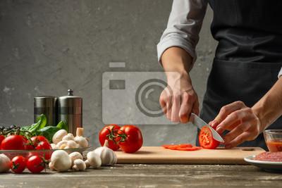 Fototapeta Pojęcie żywienia. Szef kuchni kroi pomidory na tle betonowej ściany, ze składnikami do gotowania pizzy, sosem do pizzy, sosem do włoskiego makaronu