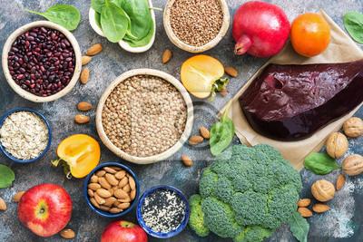Fototapeta Pokarmy bogate w żelazo. wątroba, brokuły, persimmon, jabłka, orzechy, rośliny strączkowe, szpinak, granat. Widok z góry, płaski układ.