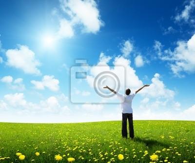 Fototapeta pole trawy i szczęśliwy młody człowiek