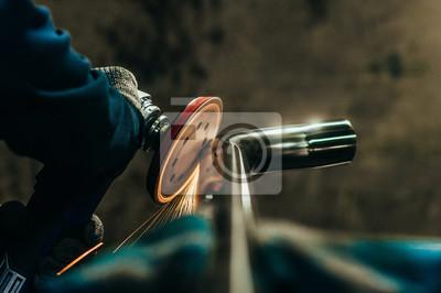 Fototapeta Polerowanie metalu za pomocą szlifierki ręcznej z tarczą polerującą. Stonowany obraz.