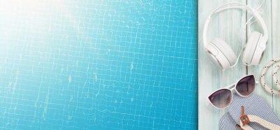 Fototapeta Pool and beach items, headphones and water surface of swimming pool