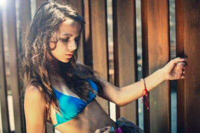 Fototapeta Portrait of a beautiful young girl in blue swimsuit leaned against a wooden fence.