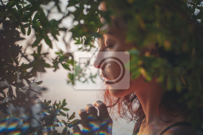 Fototapeta Portrait of a beautiful young woman with dark hair in a frame of branches and green leaves, summer and spring sensual portrait, natural beauty