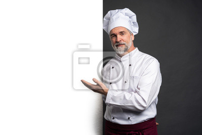 Fototapeta Portrait of a happy mature chef cook showing copyspace on the palms isolated on black background.