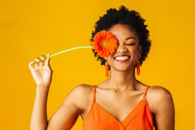 Fototapeta Portrait of a happy young woman holding orange Gerbera daisy covering her eye with eyes closed