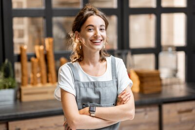 Fototapeta Portrait of a young and happy saleswoman at the counter in ice cream shop or cafe. Concept of a small business and retail