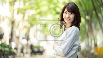 Fototapeta portrait of asian businesswoman walking in sidewalk