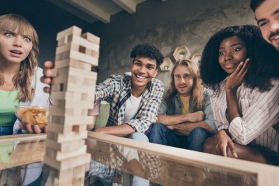 Fototapeta Portrait of attractive cheerful friends gathering playing brick game pastime in house loft brick style interior dormitory campus indoors
