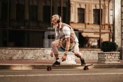 Fototapeta Portrait of bearded hipster man in white shirt on city street. Stylish happy model ride on longboard near road on buildings background