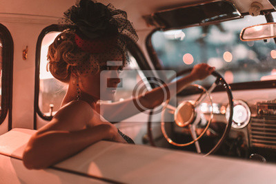 Fototapeta Portrait of beautiful sexy fashion blond girl. Model with bright makeup and curly hairstyle in retro style hat sitting in old car. Attractive woman  rides around the night city