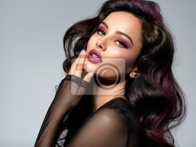 Fototapeta Portrait of beautiful young woman with bright maroon makeup. Beautiful brunette with bright cherry lipstick on her lips. Pretty girl with long black hair. Brunette with brightly colored hair.