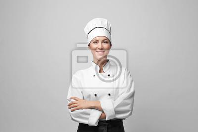 Fototapeta Portrait of female chef on light grey background