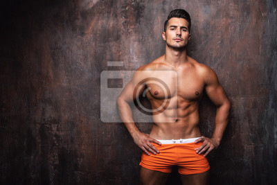 Fototapeta Portrait of handsome young man with stylish haircut in swinwear posing over rusty wall background. Perfect hair & skin. Close up. Studio shot