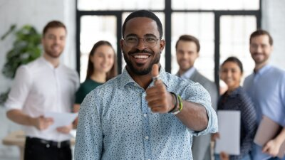 Fototapeta Portrait of happy African American male business leader making thumb up like gesture at camera. Employee satisfied with job and work with great team. Client giving positive feedback to company service