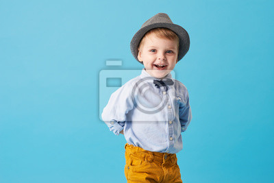Fototapeta Portrait of happy joyful  little boy isolated on blue background. Toddler child in hat and fashionable suit smiling and have a fun