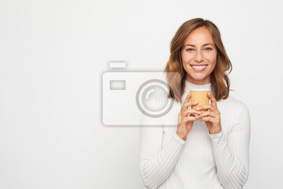 portrait of happy young woman with to go cup of coffee