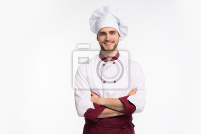 Fototapeta Portrait of positive handsome chef cook in beret and white outfit isolated on white background.