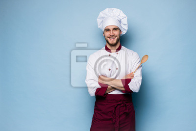 Fototapeta Portrait of positive toothy chef cook in beret, white outfit having tools in crossed arms looking at camera.