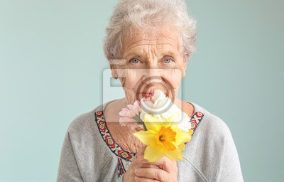 Fototapeta Portrait of senior woman with bouquet of flowers on grey background