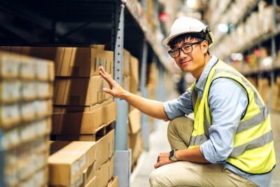 Fototapeta Portrait of smiling asian engineer man order details checking goods and supplies on shelves with goods background in warehouse.logistic and business export