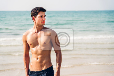 Fototapeta Portrait of smiling handsome sexy man showing muscular fit body standing on the tropical beach.Summer vacations