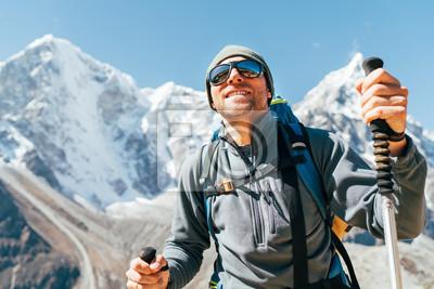 Fototapeta Portrait of smiling Hiker man on Taboche 6495m and Cholatse 6440m peaks background with trekking poles, UV protecting sunglasses. He enjoying mountain views during Everest Base Camp trekking route.