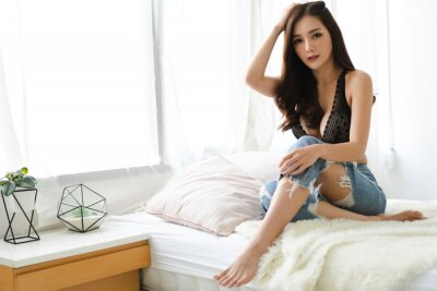 Fototapeta Portrait of smiling sexy pretty asian woman clean fresh healthy white skin posing in black underwear bra.Beautiful girl felling relaxing and enjoy time on the bed at home.Summer fashion concept