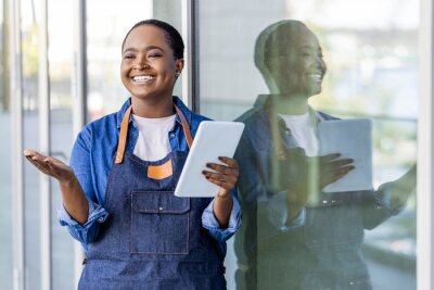 Fototapeta Portrait of woman standing at doorway of her store holding digital tablet. Cheerful waitress waiting for clients at coffee shop. Successful small business owner in casual clothing looking at camera.