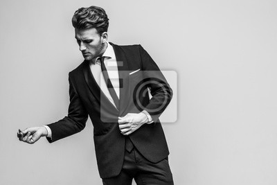 Fototapeta Portrait of young and handsome model in a classic black and white style clothing. Studio shot. Copy space.