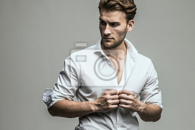Fototapeta Portrait of young and handsome model in a white shirt. Studio shot. Copy space.