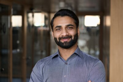 Fototapeta Portrait of young happy indian business man executive looking at camera. Eastern male professional teacher, smiling ethnic bearded entrepreneur or manager posing in office, close up face headshot.