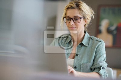 Fototapeta Portret blond kobieta pracująca w domu na komputerze przenośnym