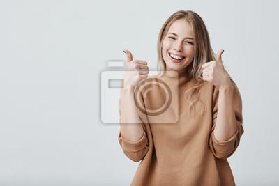 Fototapeta Portret jasnogłowy piękny żeński uczeń lub klient z szerokim uśmiechem, patrzeje kamerę z szczęśliwym wyrażeniem, pokazuje aprobaty z oba rękami, osiąga nauka cele. Język ciała
