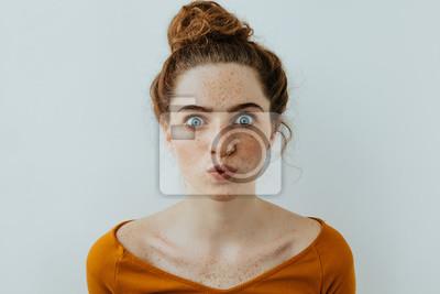 Fototapeta Portret kobiety. Styl. Piękna błękitnooka dziewczyna z piegami bieli wargi przy kamerą, na białym tle