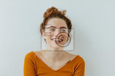 Fototapeta Portret kobiety. Szczęście. Piękna błękitnooka dziewczyna z piegami patrzeje daleko od i śmia się, na białym tle