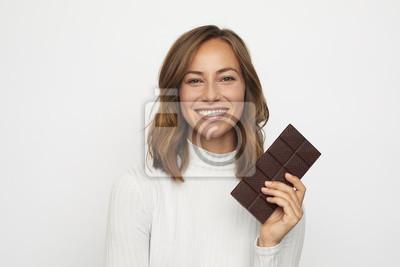 portret młodej kobiety gospodarstwa czekolady wygląda w aparacie
