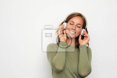 portret młodej kobiety uśmiechający się ze słuchawkami