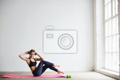 Fototapeta Portret młodej kobiety w odzież sportową, robi ćwiczenia fitness.