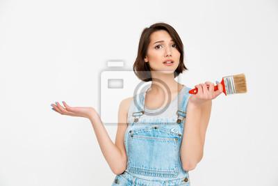 Portret młodej pięknej dziewczyny, patrząc zaskoczony, trzymając paintin
