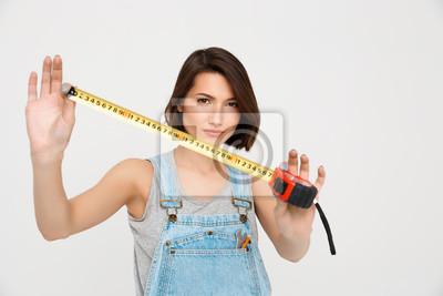 Portret młodej pięknej dziewczyny, pokazując centymetrem