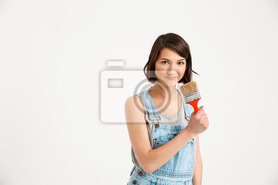 Portret młodej pięknej dziewczyny zabawy, trzymając malowanie bru