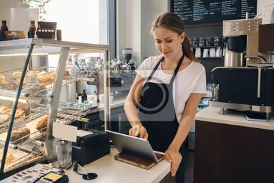Fototapeta Portret młody caucasian żeński kobieta kasjer. Sprzedawca używa panelu dotykowego do akceptowania płatności klienta. Mały biznes kawiarni bufet.