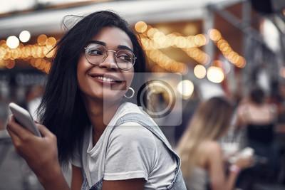 Fototapeta Portret modniś młoda dama trzyma smartphone i patrzeje daleko od z uśmiechem w szkłach. Ulica z ludźmi na zamazanym tle z bokeh skutkiem